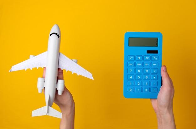 空の旅、旅行の費用の計算。手は黄色の青い電卓と旅客機の置物を持っています。