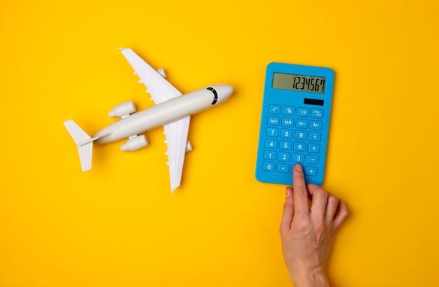 空の旅、旅行の費用の計算。青い電卓のボタンと黄色の旅客機の置物を手で押す