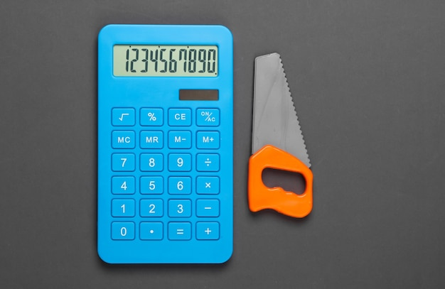 Расчет стоимости строительства дома или работы по дому. калькулятор и игрушечная пила на сером