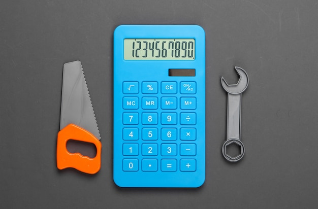 Расчет стоимости строительства дома или работы по дому, ремонтных работ. калькулятор и игрушечная пила, гаечный ключ на сером
