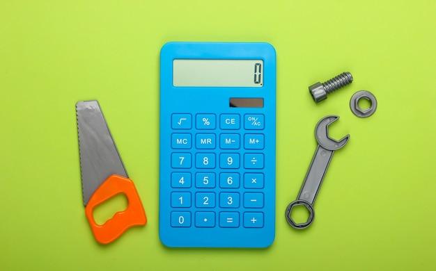 家や家事、修理作業の費用の計算。電卓とおもちゃのこぎり、緑の背景にレンチ。上面図