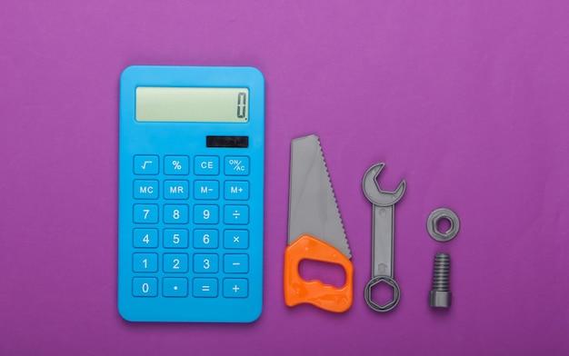 家や家事、修理作業の費用の計算。電卓とおもちゃのこぎり、紫色の背景にレンチ。上面図