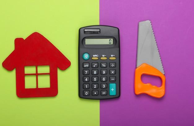 家を建てたり修理したりする費用の計算。緑紫の背景に家の置物、電卓、おもちゃのこぎり。上面図