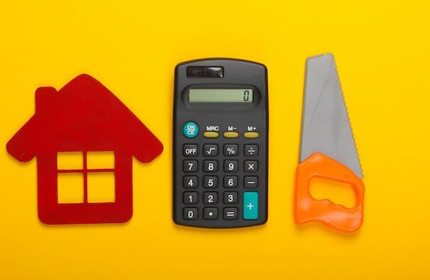 家を建てたり修理したりする費用の計算。黄色の背景に家の置物、電卓、おもちゃのこぎり。上面図