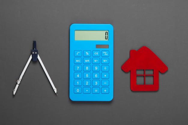 家を建てる費用の計算。赤い家の置物、電卓、灰色のコンパス
