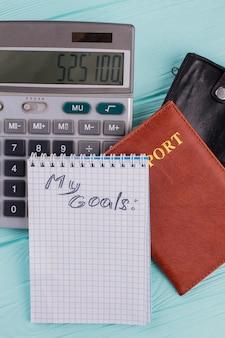 비행 및 휴가 비용 계산. 계산기와 여권의 숫자는 여행 가격의 상징입니다.