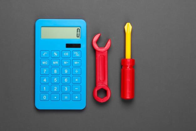 修理費用の計算。電卓とおもちゃのレンチと灰色のドライバー