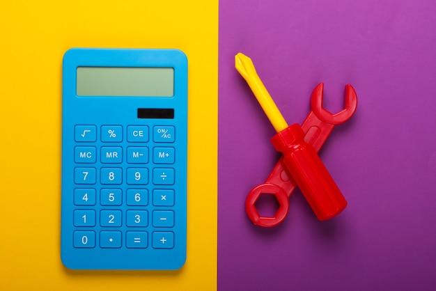 修理費用の計算。紫黄色の背景に電卓とおもちゃのレンチとドライバー。上面図