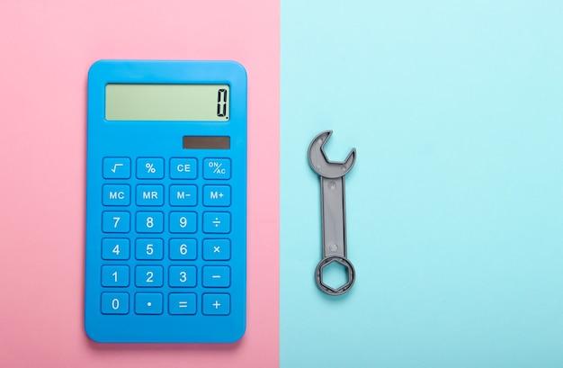 修理費用の計算。青ピンクのパステルカラーの背景に電卓とおもちゃのレンチ。上面図