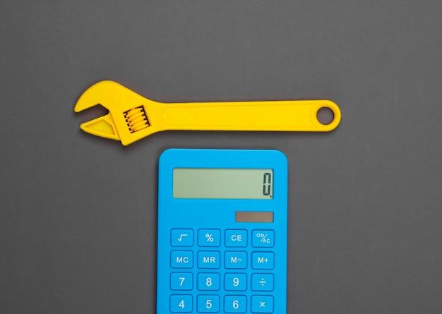 修理費用の計算。電卓と灰色のおもちゃのレンチ