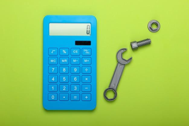 修理費用の計算。緑の背景に電卓とおもちゃのレンチ。上面図