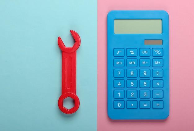 修理費用の計算。ピンクブルーのパステルカラーの背景に電卓とおもちゃのレンチ。上面図