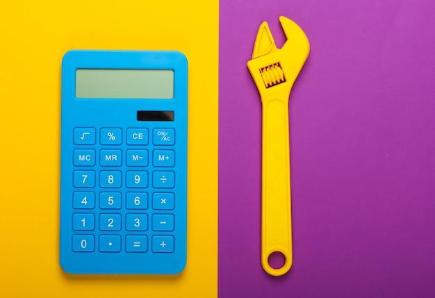 修理費用の計算。紫黄色の背景に電卓とおもちゃのレンチ。上面図