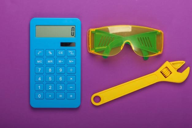 修理費用の計算。電卓とおもちゃのレンチ、紫色の背景に安全メガネ。上面図