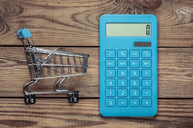 ショッピングのコストの計算。ミニスーパートロリー、木製テーブルの電卓