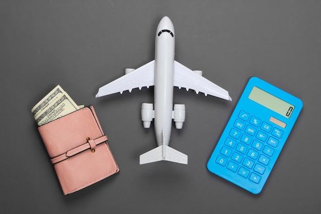 Расчет стоимости туризма или курорта. плоская планировка. фигурка пассажирского самолета, калькулятор, кошелек с кошельком на сером.