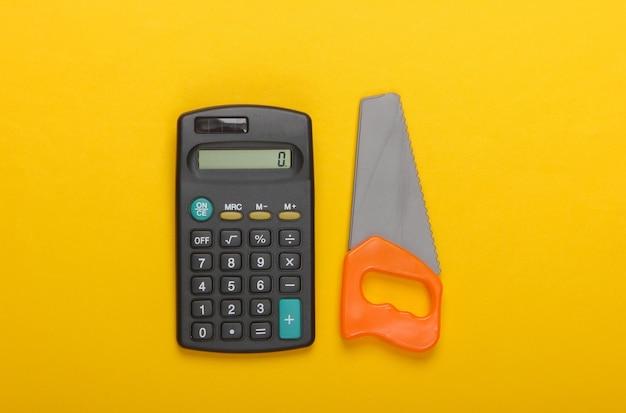 作業コストの計算。電卓と黄色の背景にミニプラスチックのこぎり。上面図
