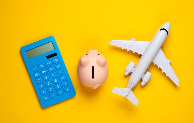 Calculation of travel expenses, economy. calculator with piggy bank, airplane on a yellow