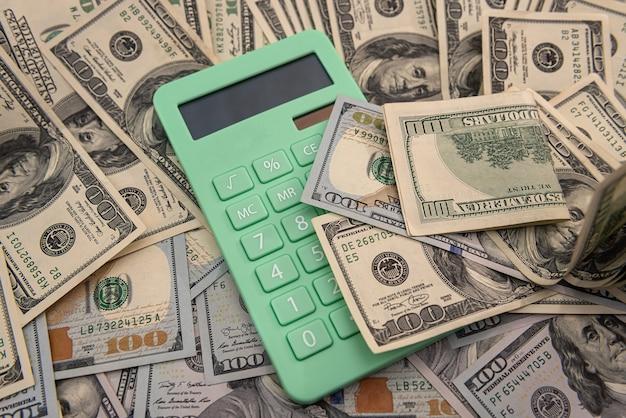 Calculator and 100 dollar bills, saving concept