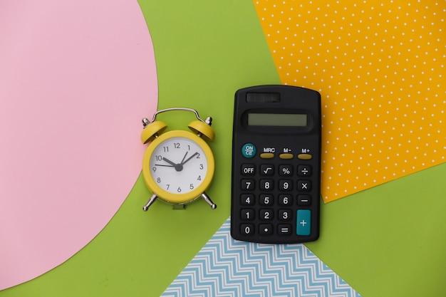 창조적 인 다채로운 종이 배경에 계산기와 알람 시계.