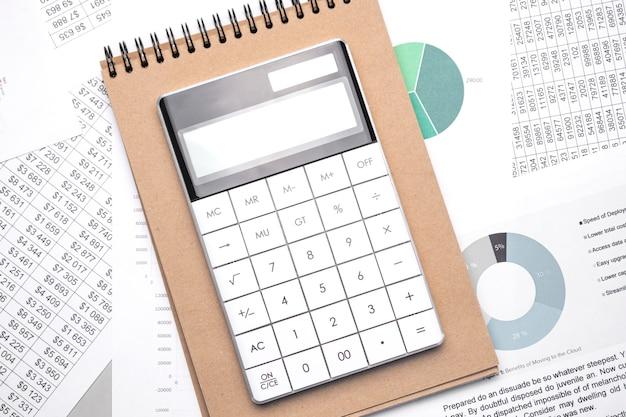 재무 지표 및 차트가있는 사무실 책상의 계산기 및 빈 메모장 페이지