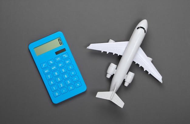 Калькулятор и фигурка пассажирского самолета на сером. расчет стоимости авиаперелета.