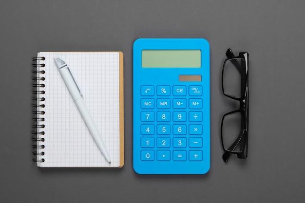 Калькулятор и очки, тетрадь на сером. секретарь, экономист или офисный работник концепции.