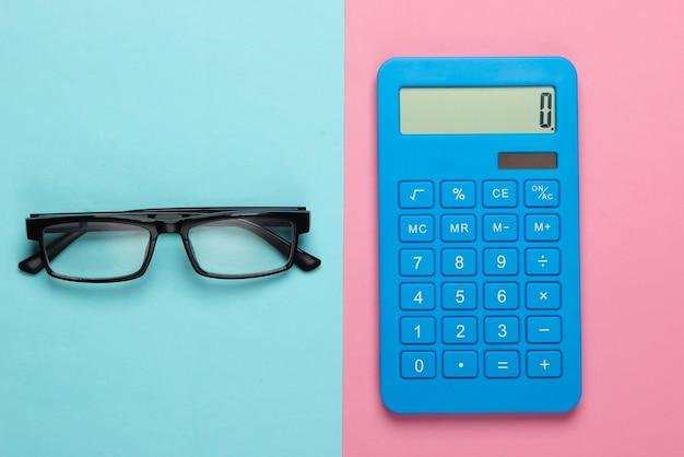 ブルーピンクのパステルカラーの電卓とメガネ。秘書、経済学者またはサラリーマンの概念。