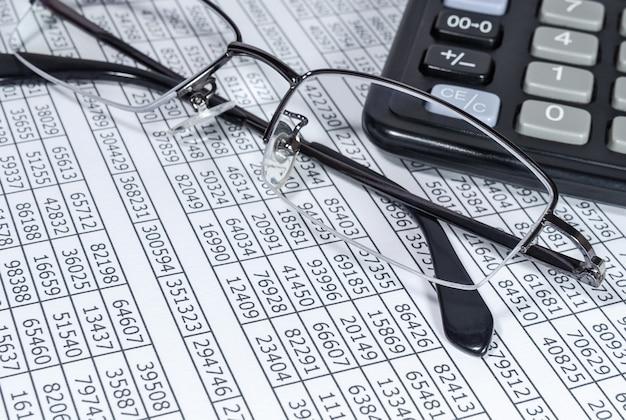 財務書類の背景に電卓とメガネ
