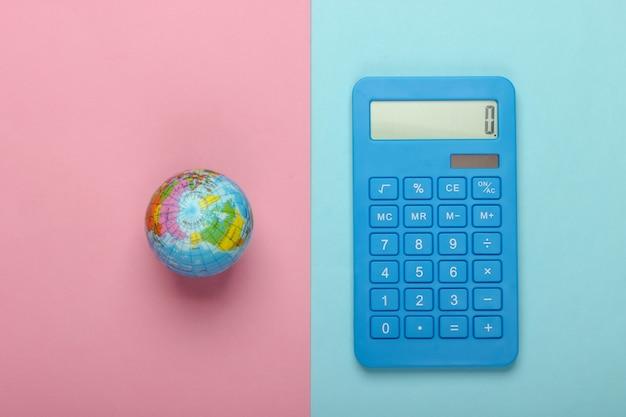 Калькулятор и глобус на сине-розовом пастельном фоне. вид сверху