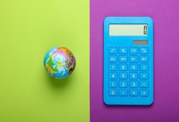 Калькулятор и глобус на зеленом фиолетовом фоне. вид сверху