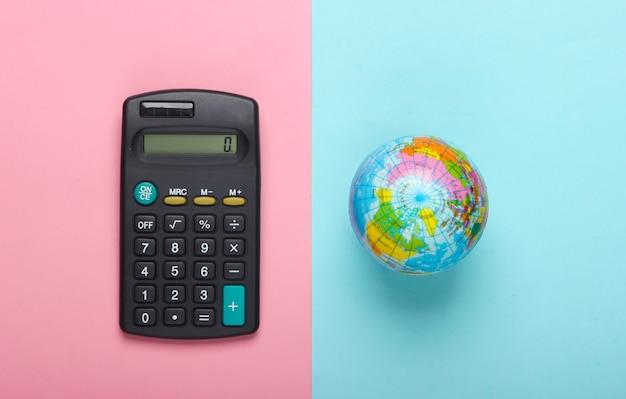 Калькулятор и глобус на розовом голубом пастельном фоне. вид сверху