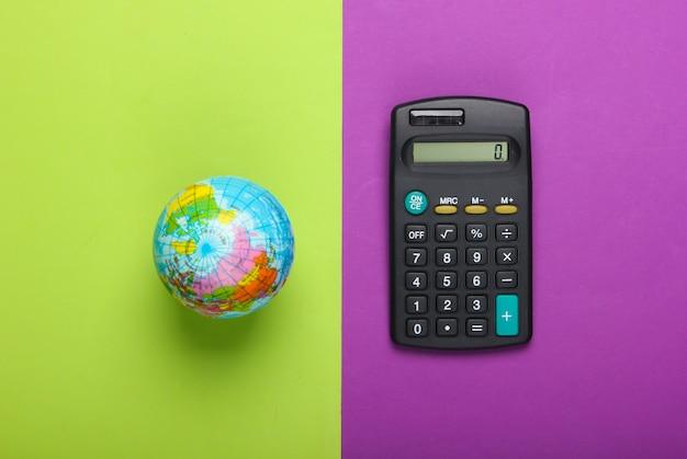Калькулятор и глобус на пурпурно-зеленом фоне. вид сверху