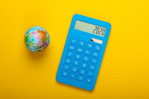 Калькулятор и глобус на желтом фоне. вид сверху