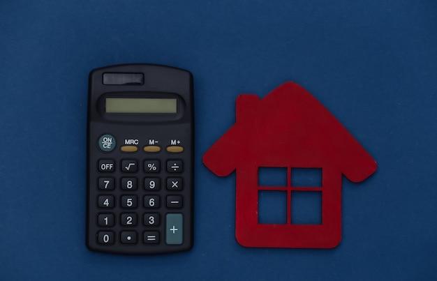 電卓と古典的な青い背景の家。カラー2020。上面図