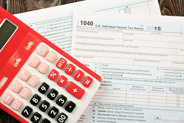 テーブルの上の計算機と個人所得税申告書