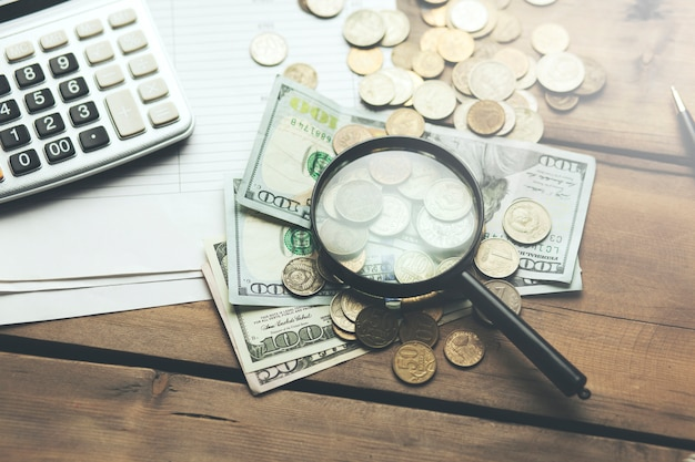 Калькулятор и лупа на банковской книжке с долларовой купюрой