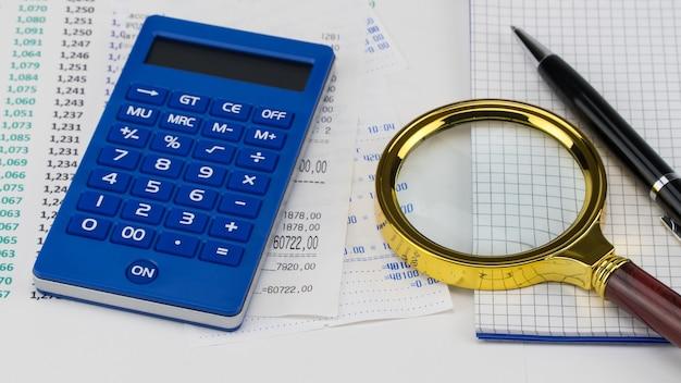 Калькулятор и лупа поверх квитанции из супермаркета. концепция покупок и оплаты