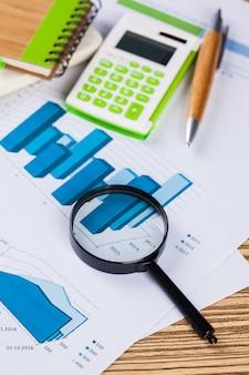 Калькулятор и увеличительное стекло на столе