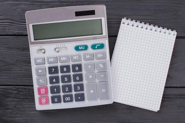 Калькулятор и блокнот на темном деревянном столе. плоский вид сверху.