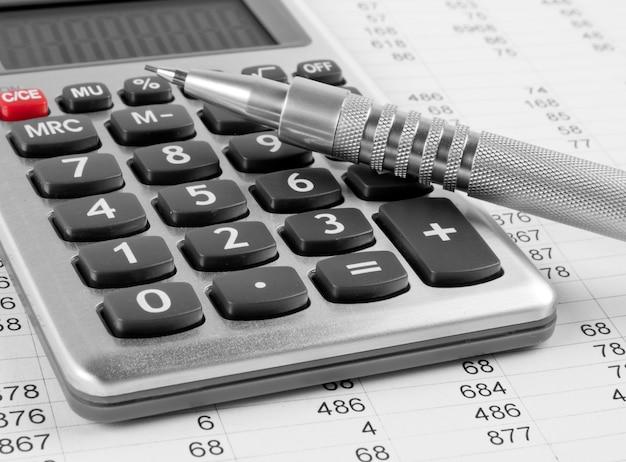 Калькулятор и ручка на деловом фоне