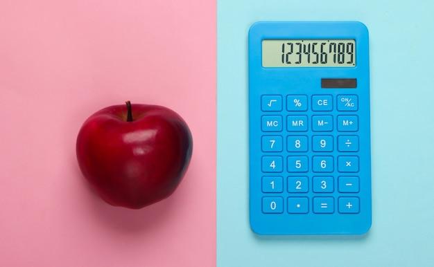 ブルーピンクのパステルカラーに電卓と赤いリンゴ。教育の概念