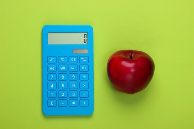 Калькулятор и красное яблоко на зеленом. концепция образования