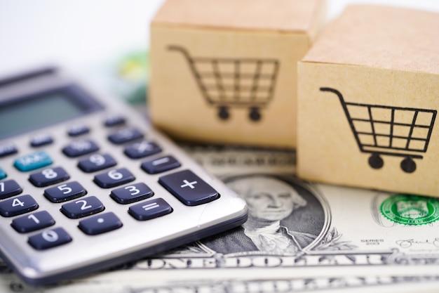 쇼핑 카트 상자 계산기와 미국 달러 지폐.