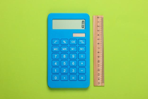 Калькулятор и деревянная линейка на зеленом. концепция образования