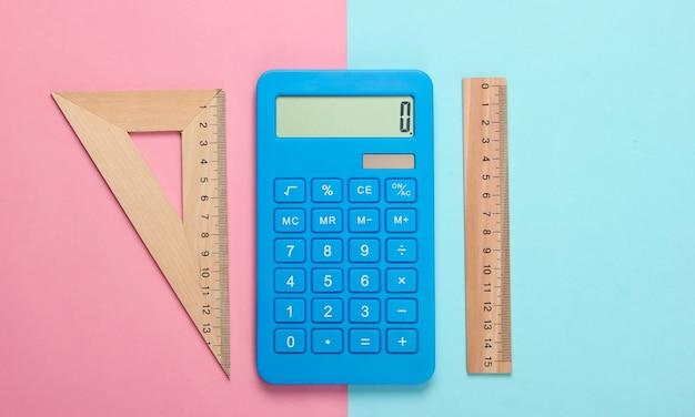 Калькулятор и деревянная линейка, треугольник на голубой пастели. концепция образования