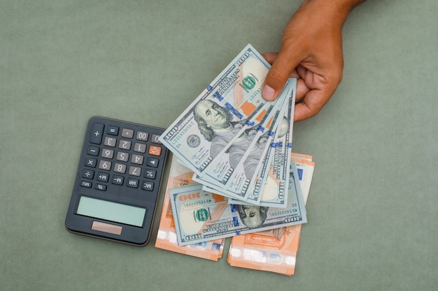 Calculator, banknotes on green grey table and man holding dollar bills.