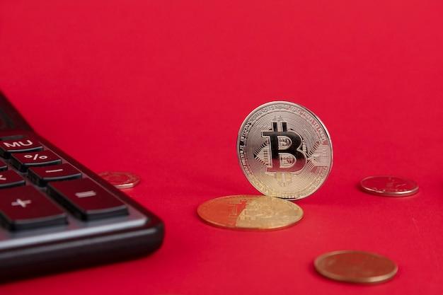 계산기, 빨간색 배경에 bitcoin 동전입니다. 공간을 복사합니다.