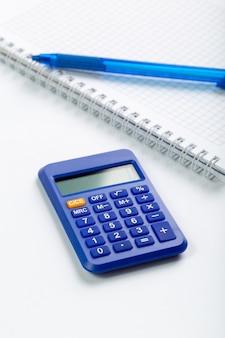 Uso blu della mano di contabilità del calcolatore per gli affari insieme al quaderno e alla penna sullo scrittorio bianco