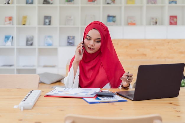 赤いヒジャーブを着て、calculator.businessと金融、オフィスの机、経済、会計上のラップトップで働く若いイスラム教徒ビジネス女性会計士